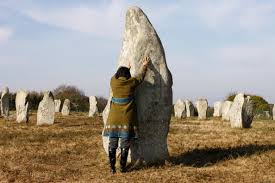 Man show his height, half that of one of Carnac's accumulator- menhirs.
